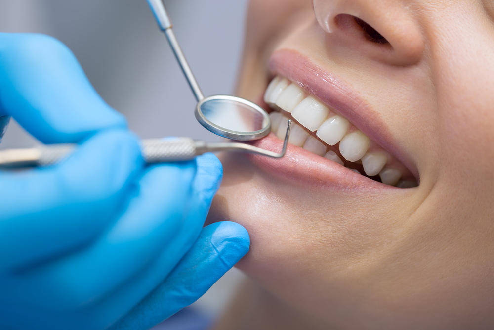 Dentist,Examining,A,Patient's,Teeth,In,The,Dentist.