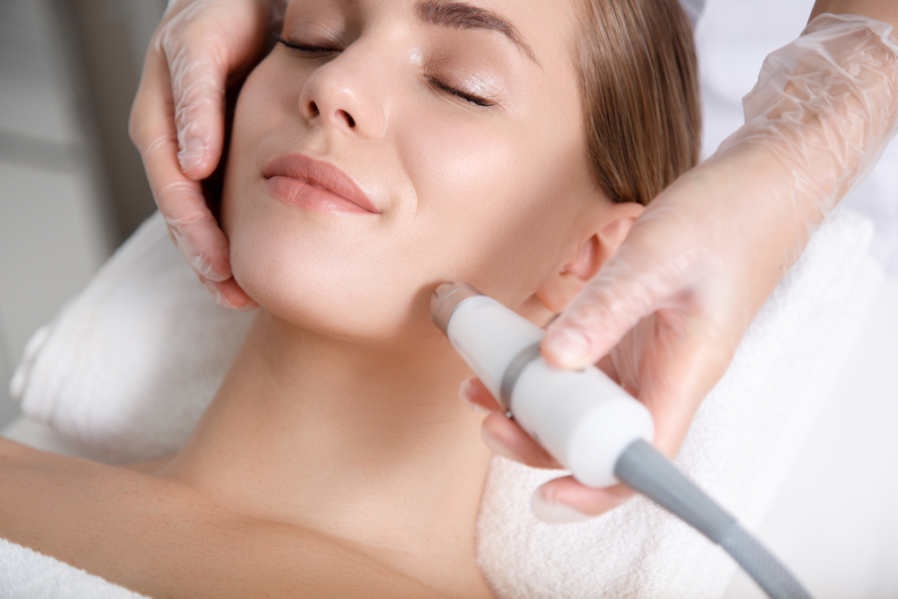 Close,Up,Of,Beautician,Hand,Making,Ultrasound,Facial,Procedure,By